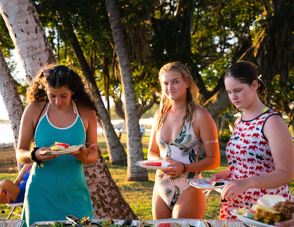 maui girls eating at a beachfront luau